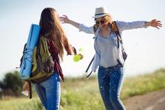 Deux beaux randonneurs de dames marchant sur la route Photographie stock libre de droits