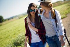 Deux beaux randonneurs de dames marchant sur la route Images stock
