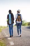 Deux beaux randonneurs de dames marchant sur la route Photo stock