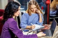 Deux belles étudiantes sont disposées pour le séminaire au café photographie stock libre de droits