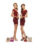 Deux belles adolescentes dans des robes rouges avec des chaussures image libre de droits