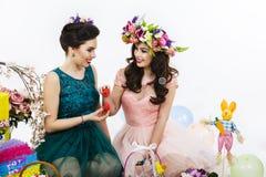 Deux belles amies avec des oeufs dans sa main et f de décoration Image stock
