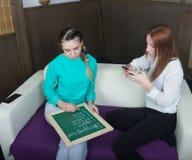 Deux belles amies détendant sur le sofa de salon pour faire des emplettes en ligne Photo libre de droits