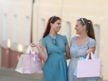 Deux belles amies dans des robes tenant des paniers dans leurs mains sur la promenade Image stock