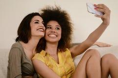 Deux belles amies de bavardage prenant le selfie avec le smartphone Images stock
