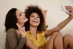 Deux belles amies de bavardage prenant le selfie avec le smartphone Photos libres de droits