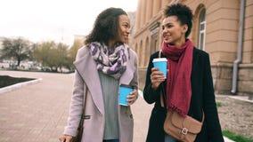 Deux belles amies de femme de métis boivent le café et des entretiens après rue de achat et de marche de ville Photographie stock libre de droits