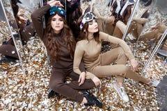 Deux belles amies de femme s'asseyent sur la pièce de paillettes de miroir de plancher Photographie stock