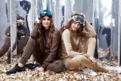 Deux belles amies de femme s'asseyent sur la pièce de paillettes de miroir de plancher Images libres de droits