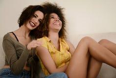 Deux belles amies de sourire de bavardage ayant l'amusement à la maison Photos libres de droits