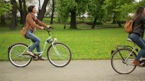 Deux belles brunes montent sur les vélos l'un après l'autre en parc de ville au printemps Jeunes femmes mignonnes dans des jeans clips vidéos