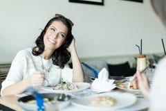 Deux belles dames mangeant dans un restaurant tout en ayant un conve Photo stock