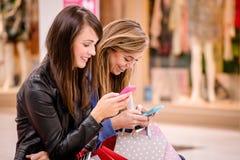 Deux belles femmes à l'aide de leur téléphone dans le centre commercial Photographie stock