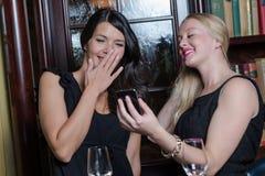 Deux belles femmes élégantes regardant un mobile Photographie stock