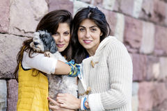 Deux belles femmes étreignant leur petit chien extérieur Photos libres de droits