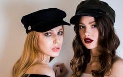 Deux belles femmes, amies, filles de blonde et de brune dans des chapeaux noirs et maquillage lumineux regardent l'appareil-photo Photos stock