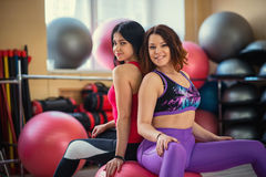 Deux belles femmes au gymnase se reposant sur une boule Images libres de droits