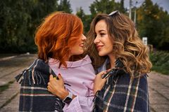 Deux belles femmes avec les cheveux rouges et bruns avec émotion communiquer couvert de couverture chaude photographie stock libre de droits