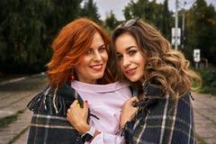 Deux belles femmes avec les cheveux rouges et bruns avec émotion communiquer couvert de couverture chaude photo stock