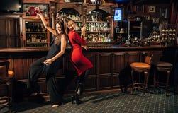 Deux belles femmes ayant l'amusement à la barre Photos stock
