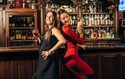 Deux belles femmes ayant l'amusement à la barre Photographie stock