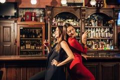 Deux belles femmes ayant l'amusement à la barre Images stock