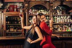 Deux belles femmes ayant l'amusement à la barre Photo stock