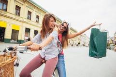 Deux belles femmes blondes faisant des emplettes sur le vélo Images stock