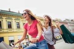 Deux belles femmes blondes faisant des emplettes sur le vélo Image libre de droits