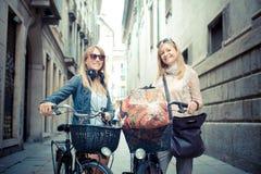 Deux belles femmes blondes faisant des emplettes sur le vélo Photographie stock libre de droits