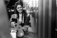 Deux belles femmes buvant du café et causant en café Image libre de droits