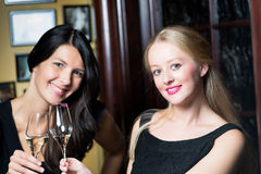 Deux belles femmes buvant du champagne sur un compteur de barre Photo stock