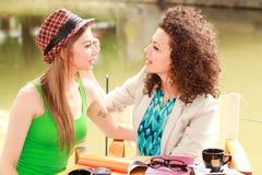 Deux belles femmes buvant le café et la causerie Photos stock