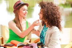 Deux belles femmes buvant le café et la causerie Images libres de droits