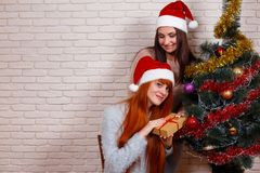 Deux belles femmes célébrant Noël dans des chapeaux de Santa avec un g Photo libre de droits
