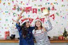 Deux belles femmes dans des chapeaux de Santa et des boîte-cadeau de se tenir ayant Photo libre de droits