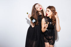 Deux belles femmes dans la nuit habillent la pose avec le champagne Photo stock