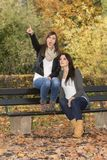 Deux belles femmes de mode de vie sur le banc en nature colorée d'automne Photos stock