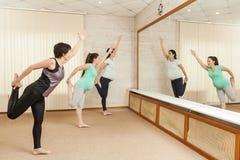 Deux belles femmes enceintes faisant le yoga avec un entraîneur Photos stock