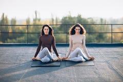 Deux belles femmes exécutent le gomukhasana méditatif de pose Image libre de droits