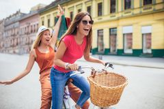 Deux belles femmes faisant des emplettes sur le vélo dans la ville Photo stock