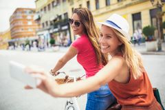 Deux belles femmes faisant des emplettes sur le vélo dans la ville Images stock