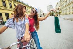 Deux belles femmes faisant des emplettes sur le vélo dans la ville Image stock
