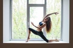 Deux belles femmes faisant l'aigle d'asana de yoga posent sur le filon-couche de fenêtre Photographie stock libre de droits