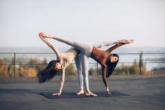 Deux belles femmes faisant l'asana Ardha Chandrasana de yoga Images stock