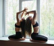 Deux belles femmes faisant l'asana de yoga sur le filon-couche de fenêtre Photographie stock