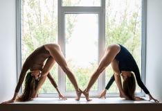 Deux belles femmes faisant l'asana de yoga sur le filon-couche de fenêtre Photo stock