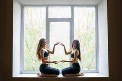 Deux belles femmes faisant l'asana de yoga sur le filon-couche de fenêtre Images stock
