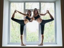 Deux belles femmes faisant le seigneur d'asana de yoga de la danse posent sur W Photos stock