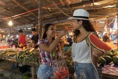 Deux belles femmes goûtant la pastèque sur le marché en plein air traditionnel dans des touristes de jeunes filles de l'Asie ache Images libres de droits
